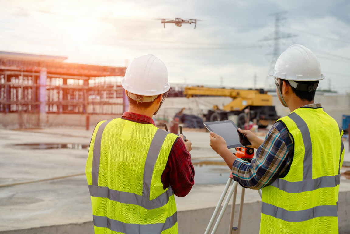 Drone operated by construction worker on building site, flying with drone.